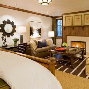 Modelo de dormitorio principal, de estilo americano, grande, con paredes blancas, moqueta, chimenea tradicional, marco de chimenea de piedra y suelo blanco