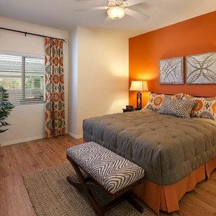 Ispirazione per una piccola camera matrimoniale classica con pareti arancioni e pavimento in bambù