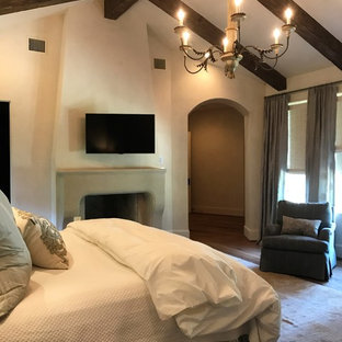Mediterranean master bedroom in Houston with beige walls, dark hardwood floors, a standard fireplace and a plaster fireplace surround.