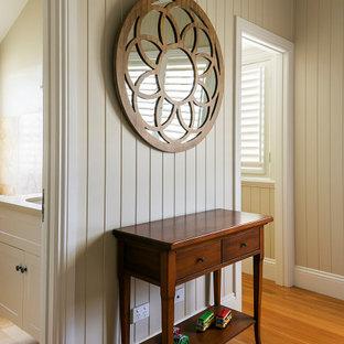 Diseño de habitación de invitados bohemia, de tamaño medio, con paredes blancas, suelo de madera clara y suelo naranja