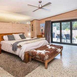 Modelo de dormitorio principal, actual, grande, con suelo de cemento, estufa de leña, marco de chimenea de piedra y suelo multicolor
