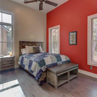 Imagen de habitación de invitados de estilo de casa de campo, de tamaño medio, sin chimenea, con paredes rojas, suelo de madera en tonos medios y suelo marrón