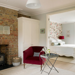 ロンドンの広いヴィクトリアン調のおしゃれな主寝室 (グレーの壁、淡色無垢フローリング、レンガの暖炉まわり、薪ストーブ、ベージュの床) のレイアウト