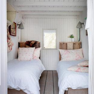 Immagine di una camera da letto costiera con pareti bianche e parquet chiaro
