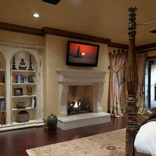 Exempel på ett stort medelhavsstil huvudsovrum, med beige väggar, mörkt trägolv, en standard öppen spis och en spiselkrans i betong