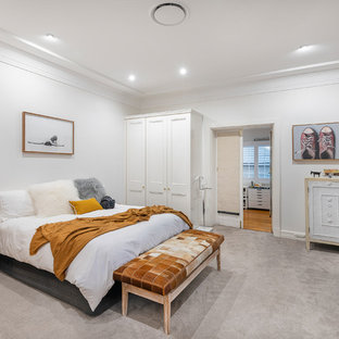 This is an example of a mid-sized country master bedroom in Brisbane with white walls, carpet and grey floor.