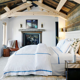 Inspiration for a mid-sized country master bedroom in New York with white walls, carpet, a standard fireplace, a wood fireplace surround, grey floor, vaulted, exposed beam, wood and wood walls.