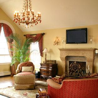 ポートランド(メイン)の大きいコンテンポラリースタイルのおしゃれな主寝室 (黄色い壁、無垢フローリング、標準型暖炉、石材の暖炉まわり) のインテリア