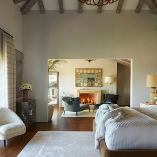 Example of a tuscan master medium tone wood floor and brown floor bedroom design in Los Angeles with gray walls and a standard fireplace