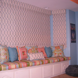 """Window Seat - This pre teens room had a wonderful, vibrant blue paint with a yummy """"creamsicle"""" trim detail on the ceiling that coordinated with a gorgeous glass light fixture in the center of the room.  The bay window had great built in drawers but needed softening and privacy at the windows.  The striped fabric on the bench was the inspiration.  It tied in the paint colors and allowed us to add lots of pattern and texture in the pillows.  The roman shades are cordless so there is never a problem with unsafe cords dangling down getting the way."""