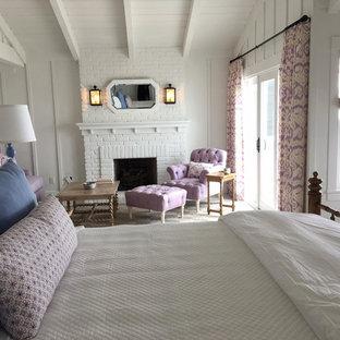 Immagine di una grande camera matrimoniale stile shabby con pareti bianche, moquette, camino classico, cornice del camino in mattoni e pavimento verde