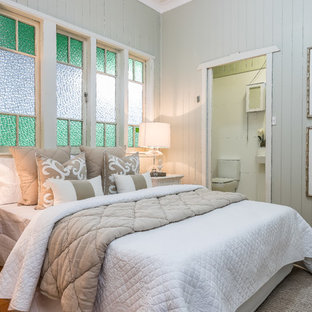 Inspiration for a country bedroom in Brisbane with grey walls, medium hardwood floors and brown floor.