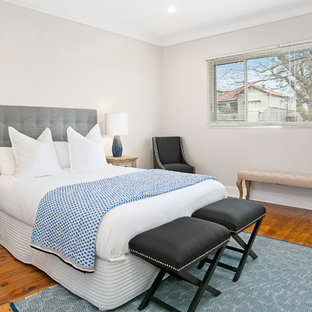 This is an example of a mid-sized transitional master bedroom in Sydney with beige walls and light hardwood floors.
