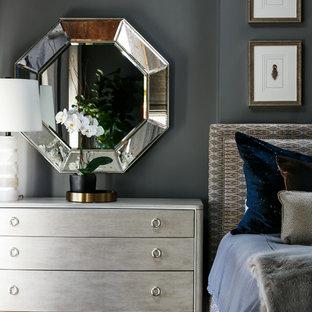 Diseño de dormitorio principal, minimalista, de tamaño medio, con paredes grises, suelo de madera en tonos medios, chimenea tradicional, marco de chimenea de madera y suelo marrón