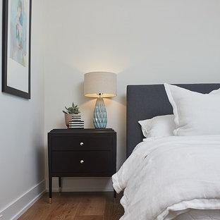 Large trendy guest medium tone wood floor and brown floor bedroom photo in Grand Rapids with beige walls