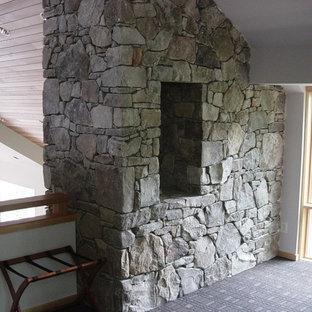 Immagine di una grande camera da letto stile loft american style con pareti bianche, moquette, camino bifacciale e cornice del camino in pietra