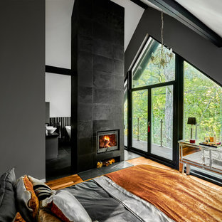 Mid-sized scandinavian master bedroom in Surrey with grey walls, light hardwood floors, a wood stove, a tile fireplace surround and brown floor.