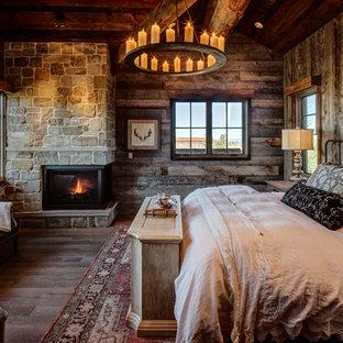 Foto de habitación de invitados rural con chimenea de esquina, marco de chimenea de piedra, suelo marrón, paredes marrones y suelo de madera oscura