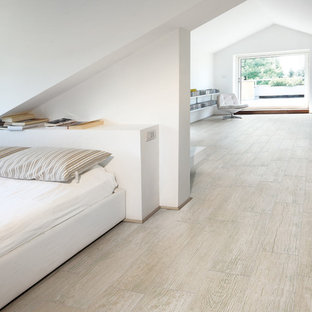 Inspiration for a large contemporary loft-style bedroom in Tampa with white walls and porcelain floors.