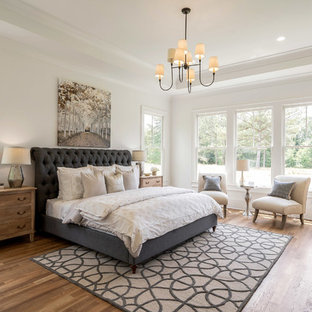 Inspiration for a cottage medium tone wood floor and brown floor bedroom remodel in Atlanta with white walls