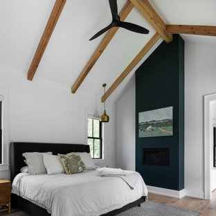 Foto på ett mellanstort lantligt huvudsovrum, med vita väggar, mellanmörkt trägolv, en standard öppen spis, en spiselkrans i gips och brunt golv