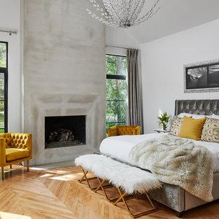 Modelo de dormitorio principal, contemporáneo, de tamaño medio, con paredes blancas, suelo de madera clara, chimenea tradicional y marco de chimenea de yeso