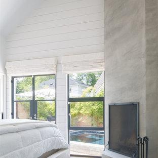 オースティンの中サイズのモダンスタイルのおしゃれな主寝室 (白い壁、無垢フローリング、コーナー設置型暖炉、漆喰の暖炉まわり、茶色い床)