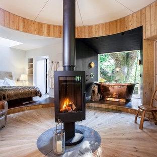 Foto di una camera da letto stile rurale di medie dimensioni con parquet chiaro, pavimento beige e stufa a legna