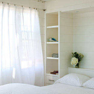 Design ideas for a small beach style guest bedroom in Boston with white walls and light hardwood floors.