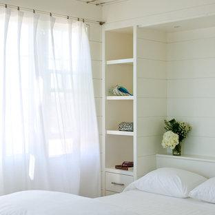 Diseño de habitación de invitados costera, pequeña, con paredes blancas y suelo de madera clara