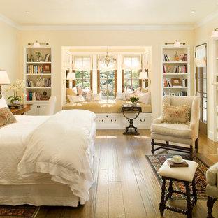 Esempio di una camera matrimoniale classica con pareti beige, pavimento in legno massello medio, camino classico e cornice del camino in pietra