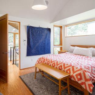 Cette photo montre une chambre parentale tendance avec un mur blanc, un sol en liège et un sol marron.
