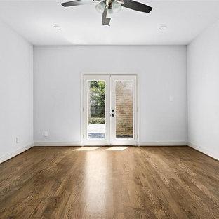 Modelo de habitación de invitados tradicional, de tamaño medio, sin chimenea, con suelo de madera en tonos medios, suelo marrón y paredes blancas
