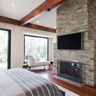 Неиссякаемый источник вдохновения для домашнего уюта: огромная хозяйская спальня в стиле модернизм с белыми стенами, паркетным полом среднего тона, двусторонним камином, фасадом камина из камня и коричневым полом