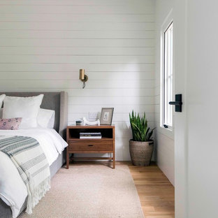 Inspiration for a farmhouse master light wood floor and beige floor bedroom remodel in Austin with white walls
