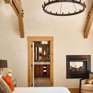Foto di una camera da letto rustica con pareti beige, pavimento in legno massello medio e camino bifacciale
