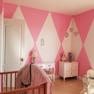 Inspiration for a large victorian guest bedroom with pink walls, medium hardwood floors and white floor.