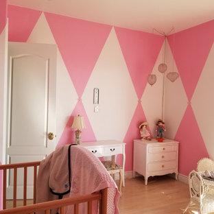 Ejemplo de habitación de invitados clásica, grande, con paredes rosas, suelo de madera en tonos medios y suelo blanco