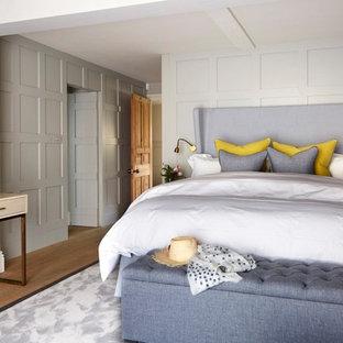 Medium sized classic bedroom in Sussex with beige walls, medium hardwood flooring and brown floors.