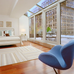 Inspiration for a master medium tone wood floor and brown floor bedroom remodel in New York with white walls