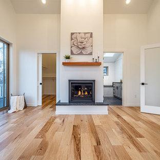 Immagine di una camera matrimoniale minimal di medie dimensioni con pareti bianche, pavimento in legno massello medio, camino classico, cornice del camino in intonaco e travi a vista