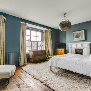 Design ideas for a mid-sized traditional master bedroom in London with blue walls, medium hardwood floors and brown floor.