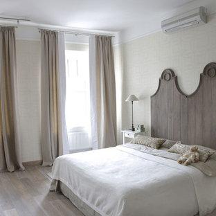 Foto de dormitorio principal, clásico renovado, grande, sin chimenea, con paredes beige y suelo de madera clara