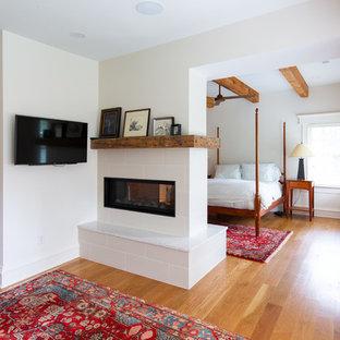 На фото: хозяйские спальни среднего размера в стиле кантри с белыми стенами, паркетным полом среднего тона, двусторонним камином и фасадом камина из плитки