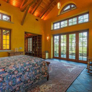 Esempio di una grande camera matrimoniale rustica con pareti gialle, pavimento in ardesia, nessun camino e pavimento nero