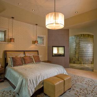 Идея дизайна: большая хозяйская спальня в стиле современная классика с бежевыми стенами, ковровым покрытием, двусторонним камином и фасадом камина из плитки