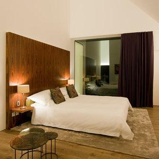 Medium sized modern master bedroom in London with white walls, light hardwood flooring and brown floors.