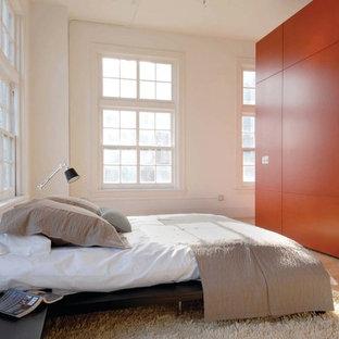 Imagen de dormitorio tipo loft, minimalista, con parades naranjas y suelo de madera clara