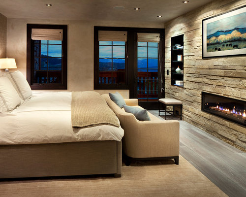 Example Of A Trendy Bedroom Design In New York With A Ribbon Fireplace And  A Stone