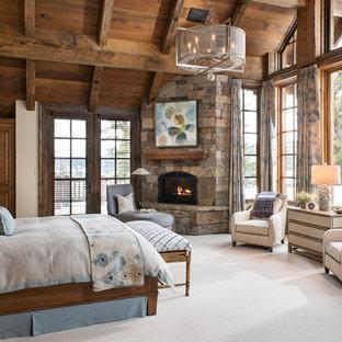 Ispirazione per una camera matrimoniale stile rurale con moquette, camino ad angolo, cornice del camino in pietra e pavimento beige